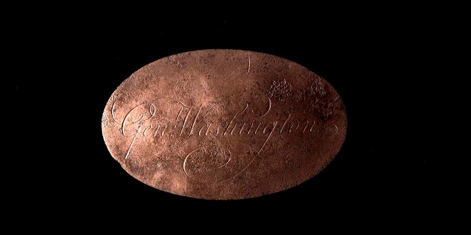 "An oval copper trunk plate engraved with ""Gen: Washington."" This remarkable artifact was recovered during the South Grove Midden excavations. (Mount Vernon Ladies' Association)"