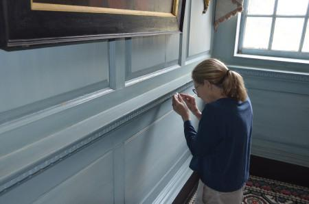 Susan Buck removing paint in the Front Parlor to examine, MVLA.