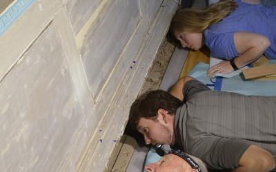 Investigating the framing behind the east wall's wood paneling.