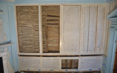 A glimpse behind the east wall paneling.