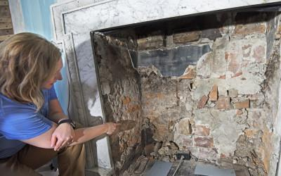 Investigating 18th-century brickwork after removal of the fireback.