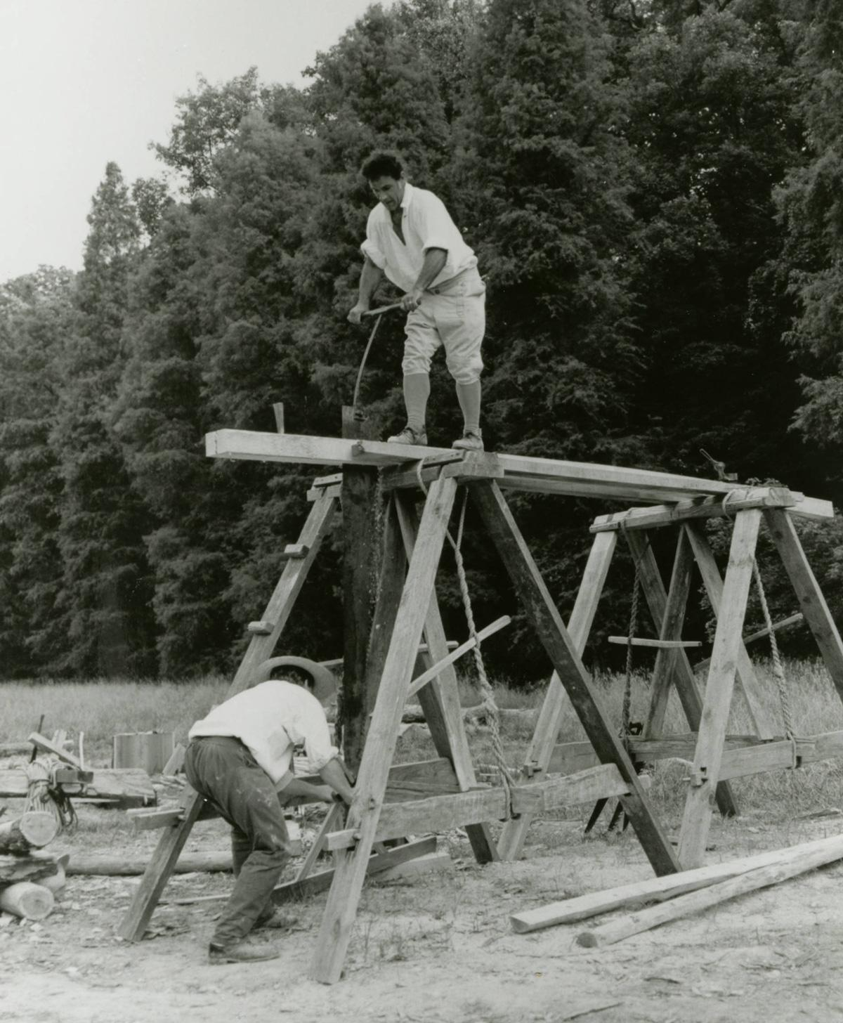 Pit sawing a framing member using colonial tools and techniques for reconstruction of the 16-sided treading barn in 1996.