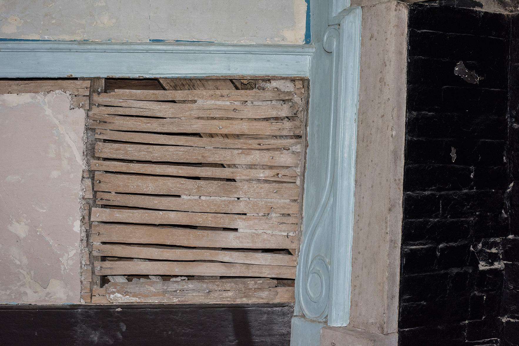 Plaster removed from the east wall of the Chintz Room uncovered an old shingle (seen just above the baseboard) used to repair the shift in the wall.  The shingle is nailed in using handmade wrought nails that date the repair to George Washington's lifetime.